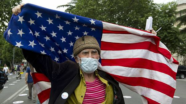 An elderly activist, wearing a face mask to protect against coronavirus, waves the US flag during a rally in Tbilisi, Georgia