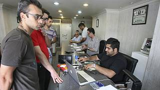 Iranians exchange currencies in a money exchange bureau, in downtown Tehran, Iran