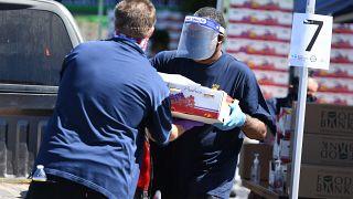 متطوعون يحمّلون مواد البقالة المجانية في السيارات للمحتاجين في أحد بنوك الطعام في حي كرينشو في لوس أنجلوس خلال جائحة فيروس كورونا