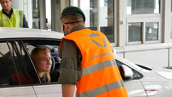 A woman crossing the Austrian border from Slovenia gets her temperature checked.