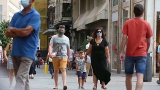 Una familia con mascarillas caminando por la calle