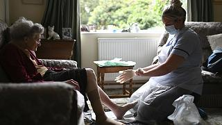 A district nurse changes the dressings on the legs of 86-year-old Margaret Ashton during a home visit.