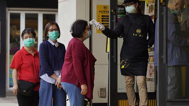 Customers receive temperature check at a restaurant in Hong Kong Tuesday, April 14, 2020.