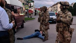 An assailant, who seized a bus with 13 hostages, lies on the ground after police officers detained him in the city centre of Lutsk, some 400 kilometres west of Kyiv, Ukraine