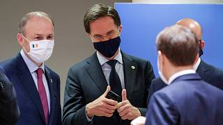 Dutch Prime Minister Mark Rutte, centre, speaks with French President Emmanuel Macron and Ireland's Prime Minister Micheal Martin, at the EU summit in Brussels, Tuesday