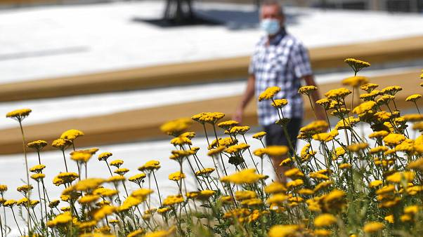 A man wearing a face mask to protect against coronavirus walks in downtown Belgrade, Serbia.
