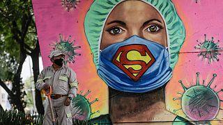 Un jardinero trabaja junto a un mural del artista urbano Applez, en Ciudad de México