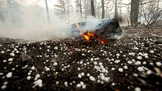 A log keeps burning as hail lies on the ground near Susanville, California. July 21, 2020