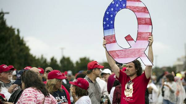 David Reinert holding a Q sign waits in line with others to enter a campaign rally with President Donald Trump and U.S. Senate candidate Rep. Lou Barletta, August 2018