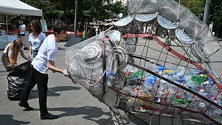 Des enfants mettent des bouteilles en plastique dan un collecteur en forme de poisson dans le centre de Budapest, le 20 juillet 2020