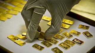A gold press operator collects 10 gram gold blanks