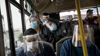 Commuters, wearing protective face masks and face shields, travel on a public bus in Lima, Peru, Wednesday, July 22, 2020.