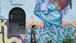 رجل يمشي أمام لوحة جدارية تشيد بالعاملين في مجال الرعاية الصحية خلال جائحة كوفيد-19 في تورونتو، كندا