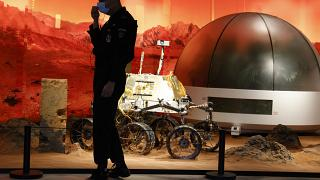 A security guard adjusts his mask near an exhibition of rovers and bio-domes on Mars in Beijing Thursday, July 23, 2020.