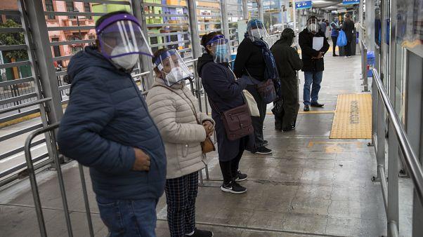 Peruanos esperan la llegada de un autobús en una parada de Lima
