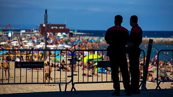 Police officers guard a barrier to stop people entering the beach, in Barcelona, Spain, Saturday, July 18, 2020.