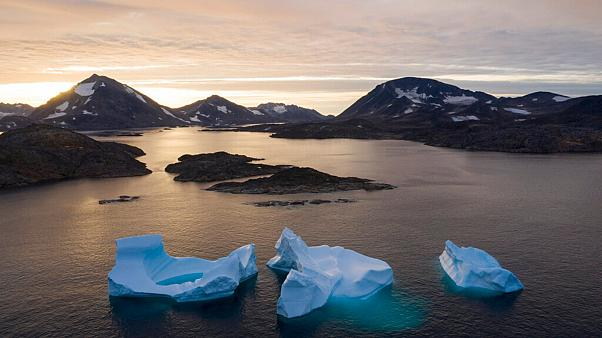 In this Aug. 16, 2019, photo, large Icebergs float away as the sun rises near Kulusuk, Greenland.