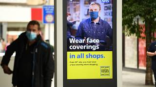 Un hombre con mascarilla en Leeds, ante un cartel anunciando que será obligatoria en comercios