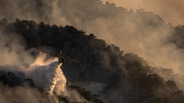 A firefighting airplane drops water on a hill near the area of Kehries, near Corinth