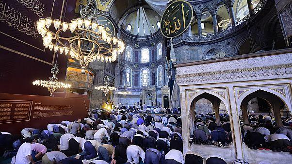 People pray inside the Byzantine-era Hagia Sophia, with sail-like drapes, top, covering Christian mosaics,