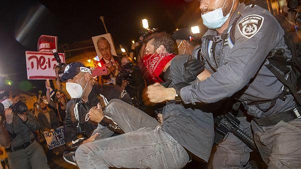 Israeli police officers arrest a demonstrator during a protest against prime minister Benjamin Netanyahu