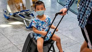 A small boy wearing a mask sits on a suitcase at the airport in Frankfurt, Germany. July 24, 2020.