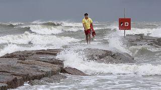 Galveston Island Beach Patrol lifeguard Matthew Herdrich walks along rocks as waves kicked up by Tropical Storm Hanna wash over them.