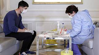 A health official takes samples for a coronavirus test from a journalist in Bucharest, Romania, March 13, 2020.