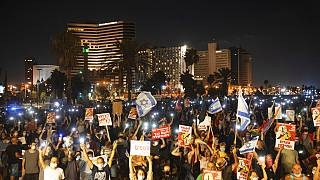 Protesters hold signs during a protest against Israel's Prime Minister Benjamin Netanyahu in Tel Aviv, Israel, on July 25, 2020