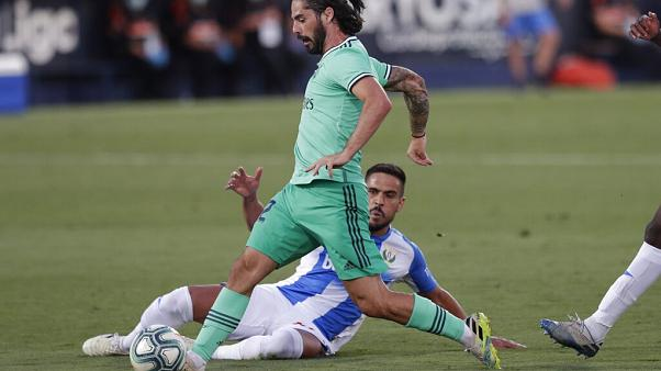 Real Madrid's Isco, is tackled by a Leganes' player during the Spanish La Liga soccer match between Leganes and Real Madrid.