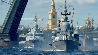 Russian warships sail on the Neva river during the Navy Day parade in Saint Petersburg.