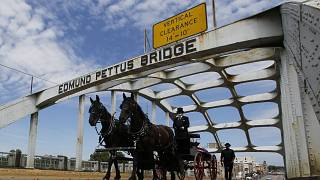 The casket of Rep. John Lewis moves over the Edmund Pettus Bridge by horse drawn carriage during a memorial service.