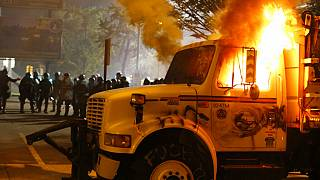 Police stand in front of a utility vehicle that was set on fire by protesters during a demonstration in Richmond, Virginia, July 25, 2020