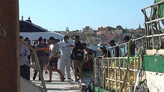 Un gruppo di migranti sbarca da un pescherecchio a Lampedusa