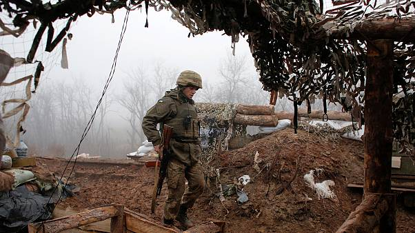 In this archive photo dated December 9, 2019, a Ukrainian soldier takes position on the front line at the town of Novoluhanske in the Donetsk region, Ukraine