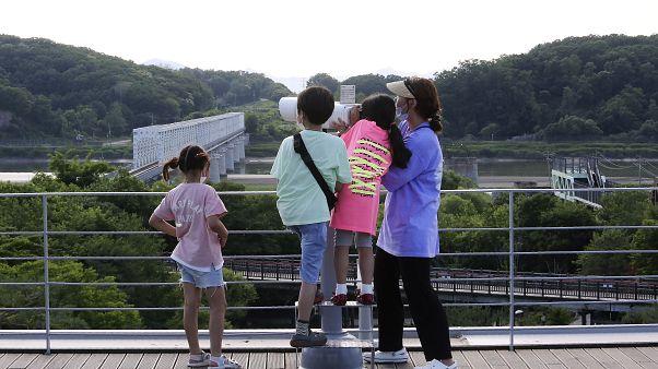 عائلة تنظر إلى الشطر الشمالي في باجو، كوريا الجنوبية، بالقرب من الحدود مع كوريا الشمالية، يونيو 2020.