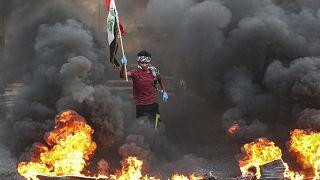 متظاهرون يحرقون إطارات أمام مبنى مجلس المحافظة خلال مظاهرة في البصرة، يوليو 2020