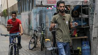 شعبان حمودة (يمين) حاملاً فنجانيْ قهوة بينما يتحضر أحد موظفيه إلى الانطلاق على دراجته الهوائية لخدمة زبائن