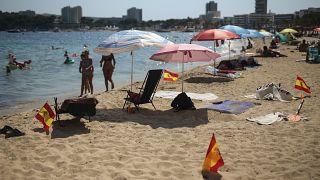 Las banderas españolas se usan como señal de distanciamiento social en la arena en Palma de Mallorca, España, el domingo 26 de julio de 2020.