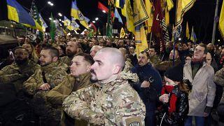 سربازان و داوطلبان اوکراینی که با جداییطلبان جنگیدهاند در حال رژه و حمل پرچم اوکراین