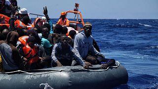 عمال الإنقاذ يساعدون في إنزال المهاجرين من زورق في البحر الأبيض، الخميس 23 يونيو 2016.