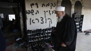 من الأرشيف: رجل فلسطيني يزور مسجدًا متضررًا في قرية دير استيا بالضفة الغربية حيث اشتعلت النيران في باب المسجد