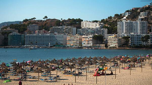 the beach in Palma de Mallorca, Spain, Sunday, July 26, 2020. Britain has put Spain back on its unsafe list and says travellers arriving in the UK from Spain must quarantine.