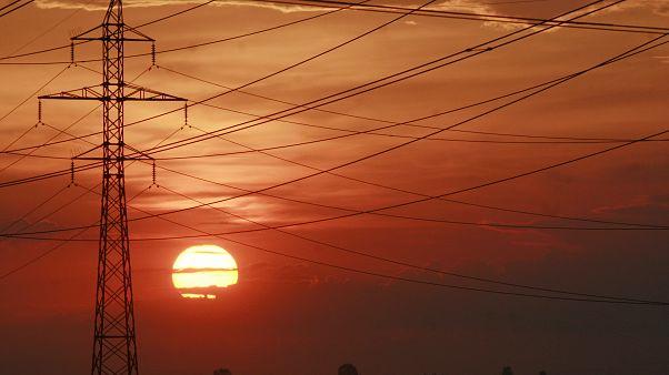 The sun sets behind power transmission lines near Kyiv, Ukraine.