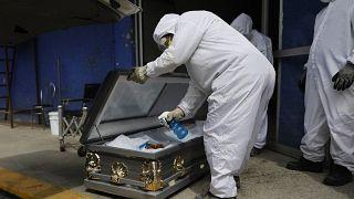 عامل من الجهاز الطبي يرشّ مطهراً داخل تابوت رجل توفي بعد إصابته بكوفيد-19