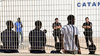 Migrants wait to be transferred to Porto Empedocle from Lampedusa, in Sicily, Monday, Aug. 19, 2019