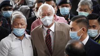 Former Malaysian Prime Minister Najib Razak, center, wearing a face mask with his supporters arrives at courthouse in Kuala Lumpur, Malaysia, Tuesday, July 28, 2020.