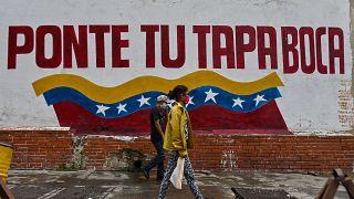 Venezolanos caminan en Caracas ante un cartel que invita a ponerse la mascarilla