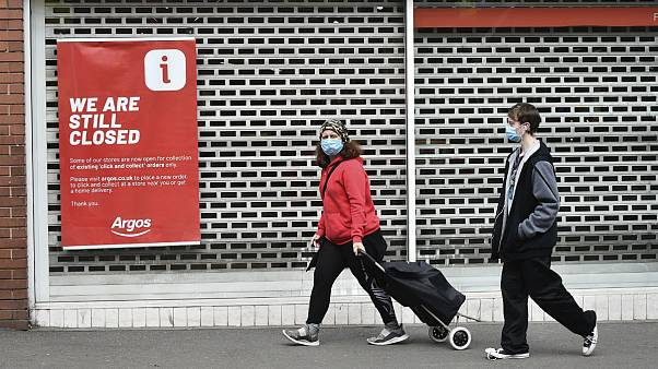 Members of the public walk past a closed shop in Leicester city centre, England