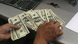 A currency exchange bureau worker, counts US dollars, in downtown Tehran, Iran
